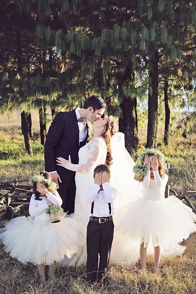 wedding couple kissing and kids having their eyes closed
